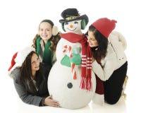 Amigos alrededor del muñeco de nieve Foto de archivo libre de regalías