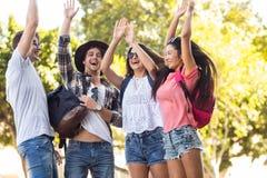 Amigos ancas que cheering acima com os braços aumentados Fotos de Stock Royalty Free