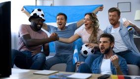 Amigos argentinos que cheering para a equipe de futebol favorita, comemorando a vitória foto de stock