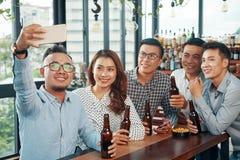 Amigos asiáticos alegres que tomam o selfie na barra fotos de stock