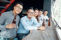 Amigos asiáticos com cerveja no contador da barra foto de stock royalty free