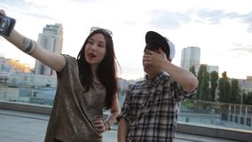 Amigos asiáticos de la raza mixta que toman el selfie con un teléfono elegante y que hacen caras de la diversión almacen de metraje de vídeo