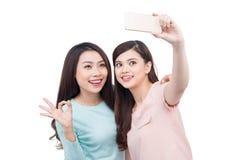 Amigos asiáticos felices de la mujer que toman un autorretrato con un pho de la célula Imágenes de archivo libres de regalías