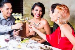 Amigos asiáticos que jantam no restaurante extravagante Fotos de Stock