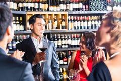 Amigos asiáticos que tuestan con el vino rojo en barra Foto de archivo
