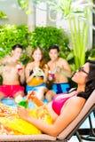 Amigos asiáticos que van de fiesta en la fiesta en la piscina en centro turístico Imagenes de archivo