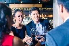 Amigos asiáticos que tuestan con el vino rojo en barra Imagenes de archivo