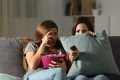 Amigos aterrorizados que ven la TV en la noche en casa Imagen de archivo