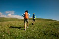 Amigos Backpacking das mulheres que caminham em montanhas da pastagem Imagens de Stock Royalty Free