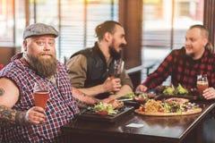 Amigos barbudos modernos que cenan en barra Imagen de archivo