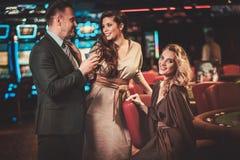 Amigos bien vestidos en un interior de lujo del casino fotografía de archivo
