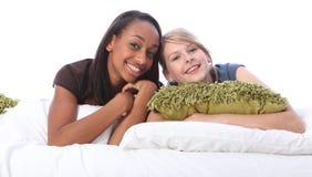 Amigos blancos y negros del adolescente que mienten en cama Fotografía de archivo libre de regalías