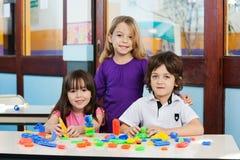 Amigos bonitos com blocos na mesa na sala de aula foto de stock royalty free