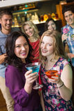Amigos bonitos que beben los cócteles juntos Foto de archivo libre de regalías