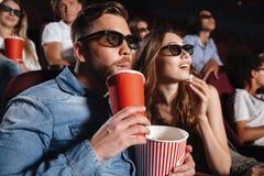 Amigos cariñosos concentrados de los pares que se sientan en cine Imagen de archivo