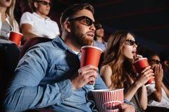 Amigos cariñosos concentrados de los pares que se sientan en cine Imágenes de archivo libres de regalías