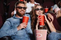 Amigos cariñosos concentrados de los pares que se sientan en cine Foto de archivo libre de regalías