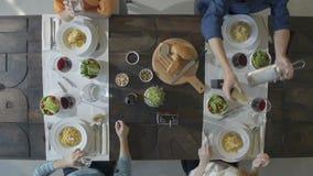 Amigos caucásicos del cuadro cuatro de arriba de visión superior que comen las pastas italianas de los espaguetis del carbonara e metrajes