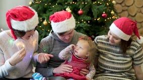 Amigos cercanos que se sientan en la alfombra con un girll del bebé, jugando con ella y la guirnalda cerca del árbol de navidad,  metrajes