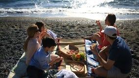 Amigos com as crianças que comem a pizza na praia Piquenique pelo mar na praia vídeos de arquivo