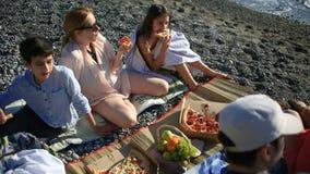 Amigos com as crianças que comem a pizza na praia Piquenique pelo mar na praia video estoque