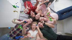 Amigos com as emoções felizes que jogam com mentira dos confetes junto e sorriso na câmera durante um partido da casa vídeos de arquivo