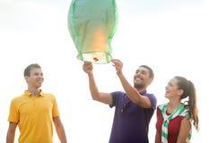 Amigos com as lanternas chinesas do céu na praia Fotografia de Stock Royalty Free
