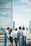Amigos com cerveja no terraço com arquitetura da cidade imagem de stock royalty free