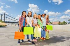 Amigos com o braço-em-braço da caminhada dos sacos de compras na cidade Foto de Stock