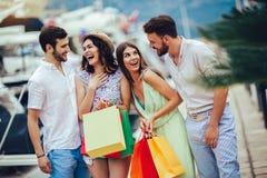 Amigos com sacos de compras que andam pelo porto de um recurso tur?stico do mar imagem de stock
