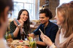Amigos com smartphones e alimento na barra ou no café Foto de Stock Royalty Free