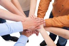 Amigos com suas mãos empilhadas junto Imagens de Stock
