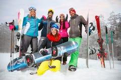 Amigos con el esquí y la snowboard el vacaciones de invierno - havin de los esquiadores Foto de archivo libre de regalías