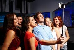 Amigos con el smartphone que toma el selfie en club Imagen de archivo libre de regalías