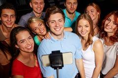 Amigos con el smartphone que toma el selfie en club Fotos de archivo libres de regalías