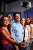 Amigos con el smartphone que toma el selfie en club Foto de archivo libre de regalías