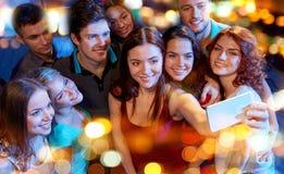 Amigos con el smartphone que toma el selfie en club Imágenes de archivo libres de regalías