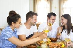 Amigos con el vino blanco que tuestan sobre la tabla servida con la comida fotografía de archivo libre de regalías