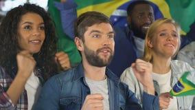 Amigos con la bandera brasileña que apoya al equipo de fútbol nacional en la barra, liga metrajes