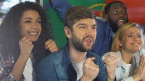 Amigos con la bandera portuguesa que apoya al equipo de deportes nacional en campeonato de la barra almacen de metraje de vídeo