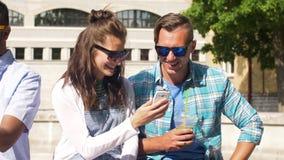 Amigos con la bebida y el smartphone en ciudad metrajes
