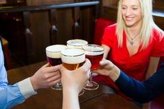 Amigos con la cerveza en un pub Fotos de archivo libres de regalías