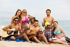 Amigos con la guitarra en la playa Fotografía de archivo libre de regalías