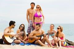 Amigos con la guitarra en la playa Fotos de archivo libres de regalías