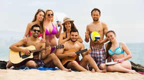 Amigos con la guitarra en la playa Foto de archivo libre de regalías