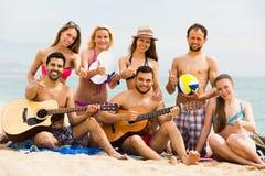 Amigos con la guitarra en la playa Foto de archivo