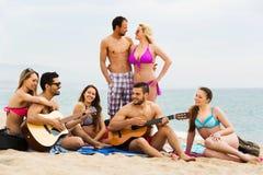 Amigos con la guitarra en la playa Imagen de archivo libre de regalías