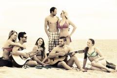 Amigos con la guitarra en la playa Fotografía de archivo