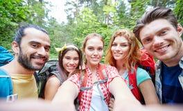 Amigos con la mochila que toma el selfie en madera Imagenes de archivo