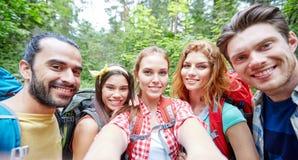 Amigos con la mochila que toma el selfie en madera Fotografía de archivo